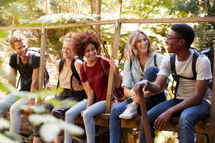 Five young adult friends on a hike sitting together talking during a break, close up