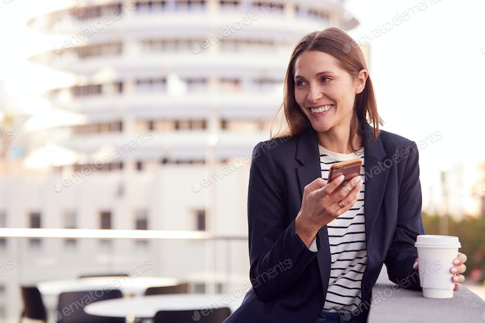 Businesswoman Standing Outside Office Building Using Mobile Phone With City Skyline In Background