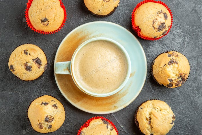 Overhead view of delicious coffee around small cupcakes on dark background