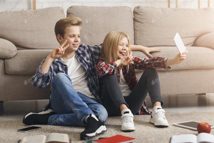 Brother And Sister Making Selfie Gesturing V-Sign Sitting On Floor