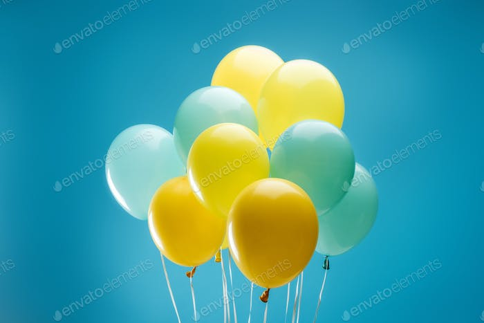 bright colorful yellow and blue balloons on blue background