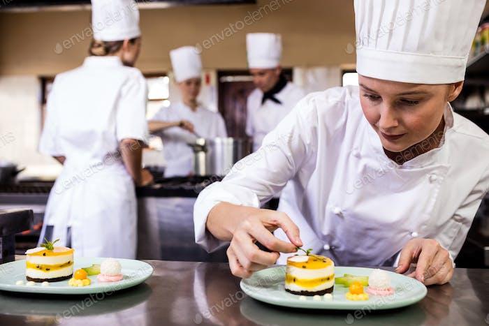 Chef femenino adornando deliciosos postres en un plato