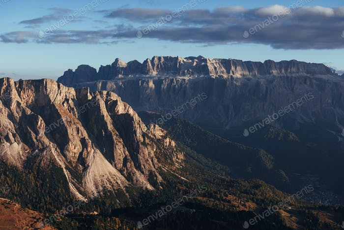 Sun began to hide. Landscape of mountains and trees below at sunny day. Italian Seceda alpes