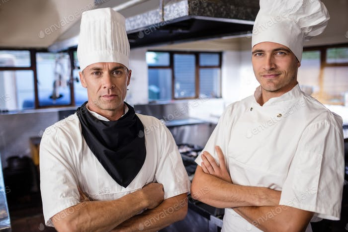 Two male chefs standing with arms crossed in kitchen at hotel