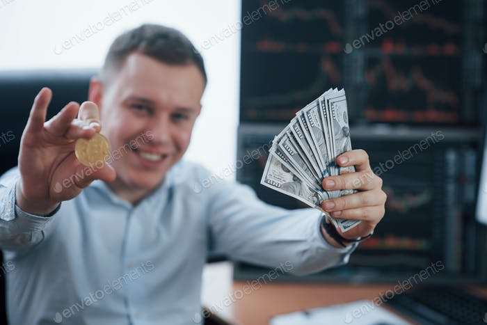 Businessman holding bitcoin and money in hands while sitting in modern office with many monitors