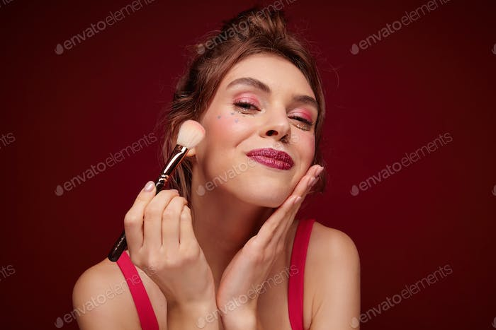 Close-up of pretty young brunette female with claret lips applying blushes