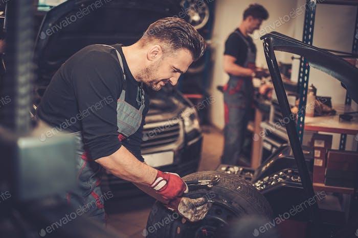 Professional car  mechanic balancing car wheel on balancer in au