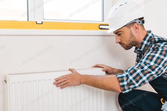 handsome handyman in helmet sitting near heating radiator