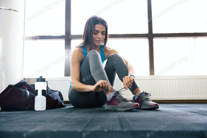 Beautiful woman tying shoelaces