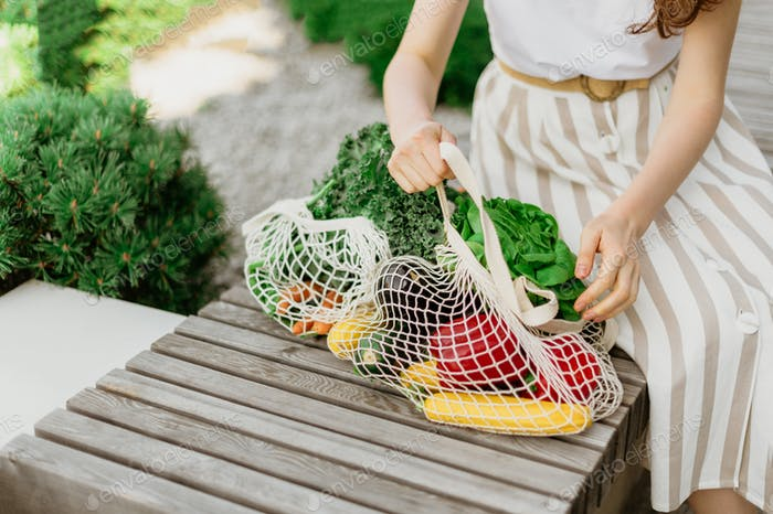 Girl holding mesh shopping bag and cotton shopper with vegetables without plastic bags, wooden