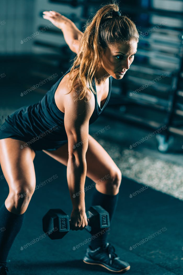 Cross training. Sporty woman exercising at the gym