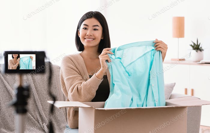 Happy asian woman recording video unpacking parcel