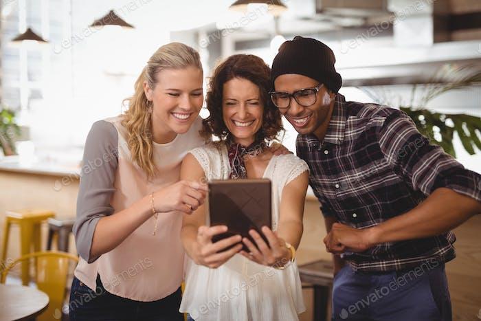 Fröhliche Multi ethnische Freunde nehmen Selfie von digitalem Tablet im Café