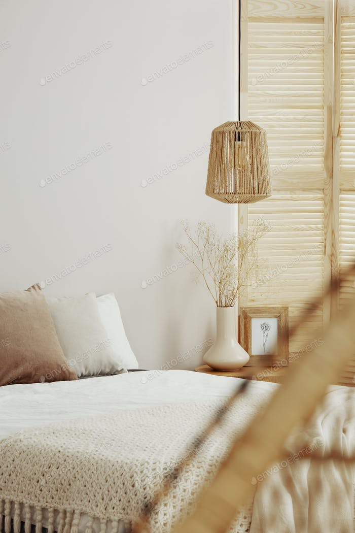 Wooden lamp in elegant white bedroom interior with furniture made of natural materials