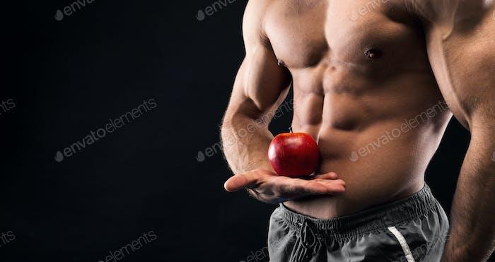Unerkennbarer Mann hält roten Apfel in seiner muskulösen Hand