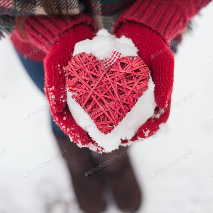 Hands in woolen mittens holding red heart