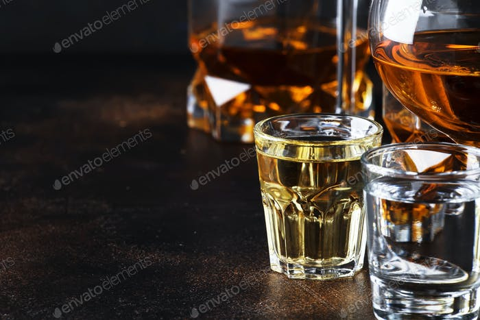 Selection of hard alcoholic drinks in big glasses and small shot glass in assortment