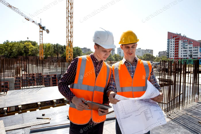 Structural engineer and construction manager dressed in orange work vests and helmets discuss