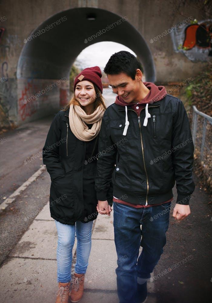 amar jóvenes pareja caminar en un calle