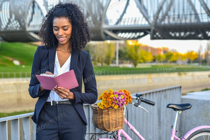 Business black woman with vintage bicycle by the river looking a