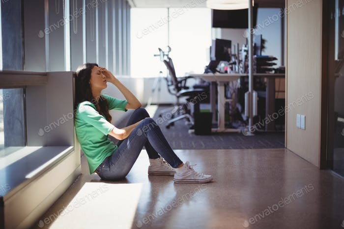 Worried female executive sitting in corridor