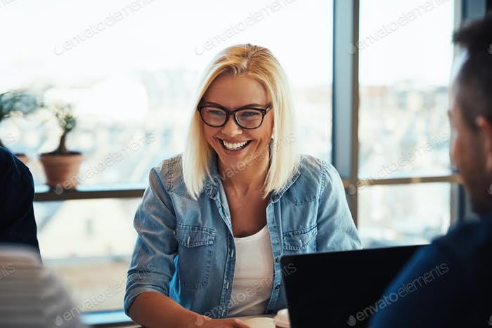 Young businesswoman laughing during a meeting with office colleagues