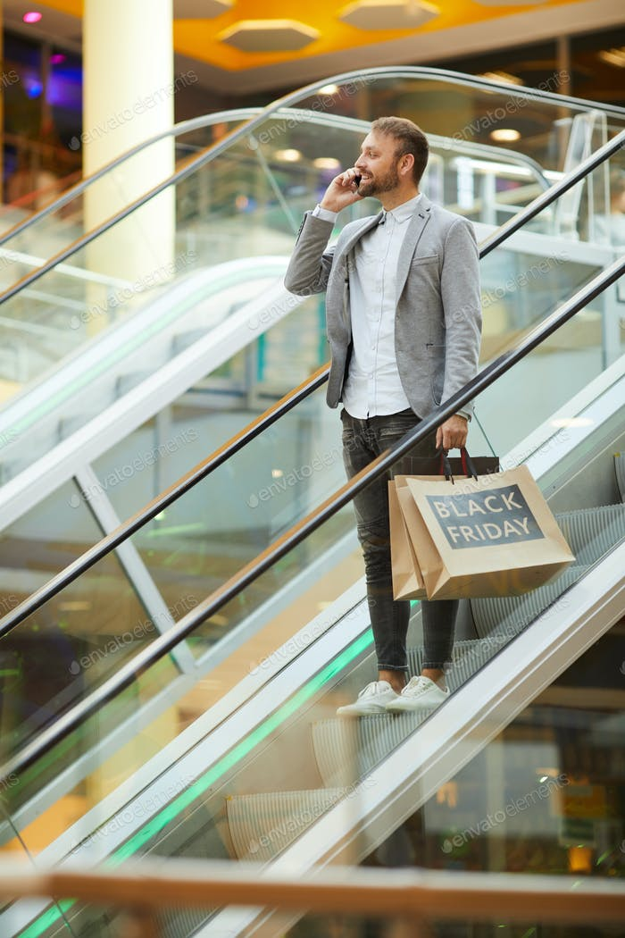 Handsome Man Speaking by Phone while Shopping
