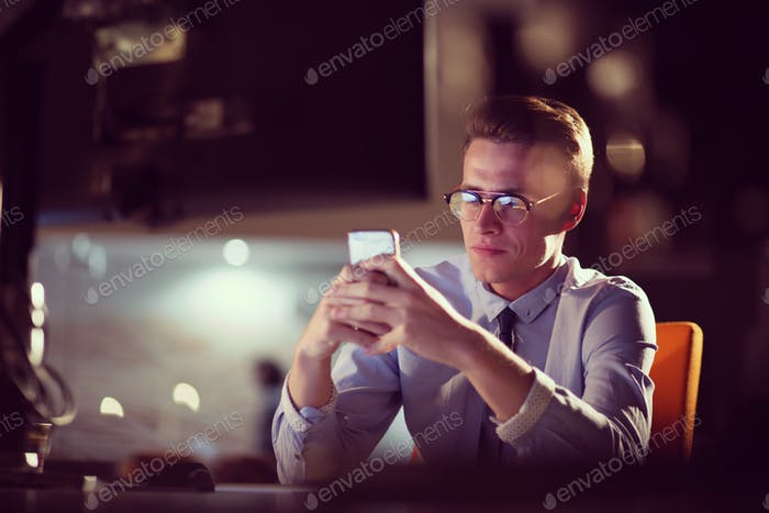 man using mobile phone in dark office