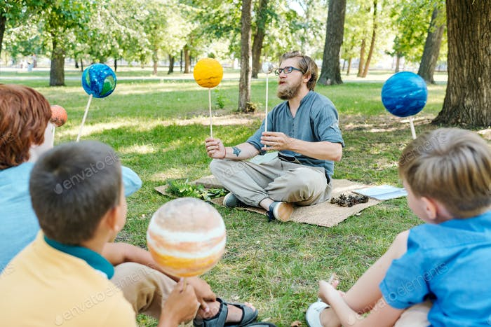 Astronomy teacher comparing planets at lesson