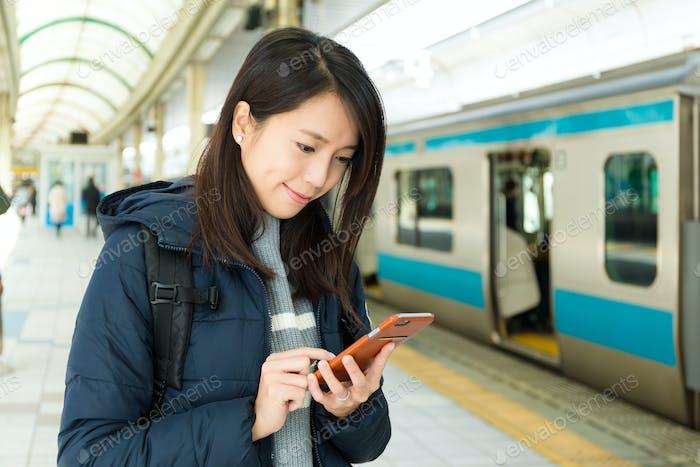 Woman read on cellphone in train platform