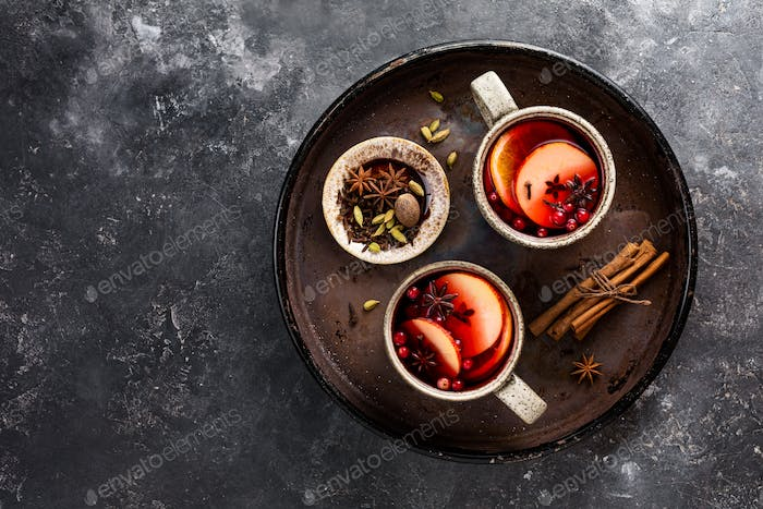 Mulled wine in big rustic mugs with spices and apple fruit