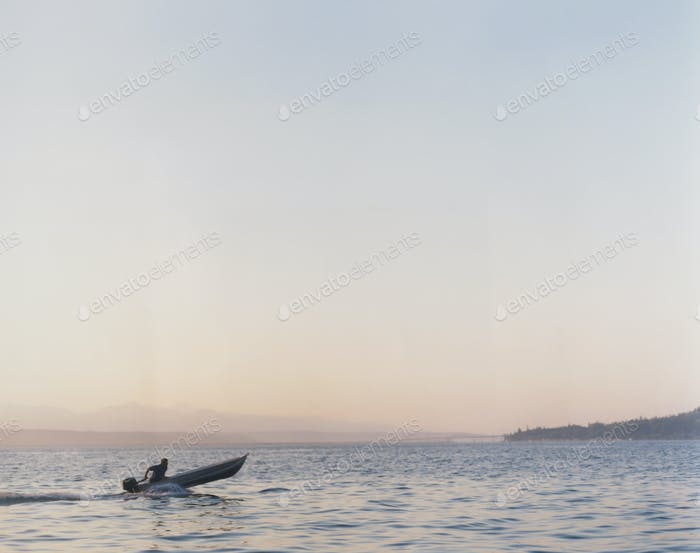 Man riding in small motorized skiff at dusk