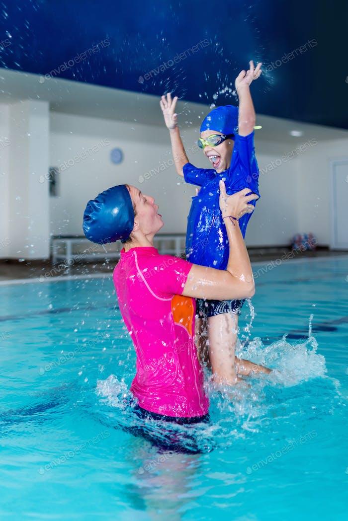Swimming school. Cute little boy having fun with swimming instru