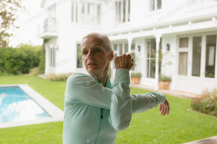 Front view of active senior Caucasian woman exercising in porch at home