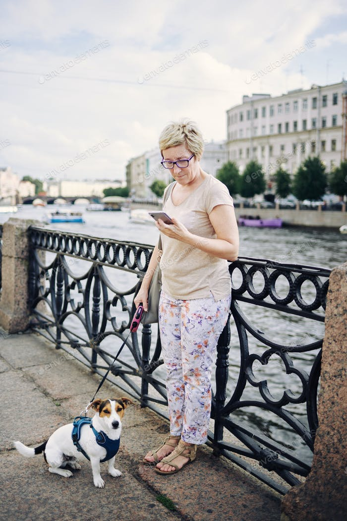 Aged woman with dog on embankment