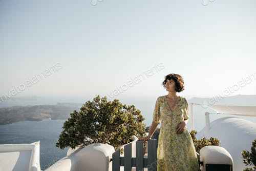 Curly charming woman in floral dress leans on fence and looks into distance. Brunette lady in summe