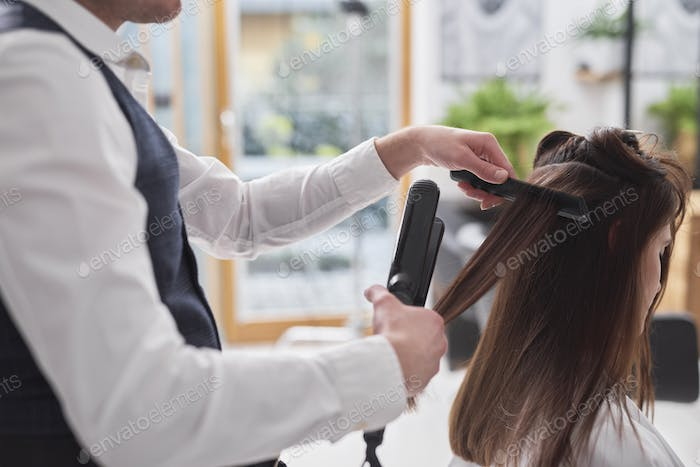Female hairdresser using comb and straightener