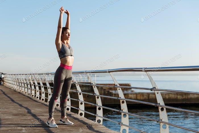 Молодая спортсменка растягивается перед утренними упражнениями. Тренировка бегуна у женщин на берегу моря