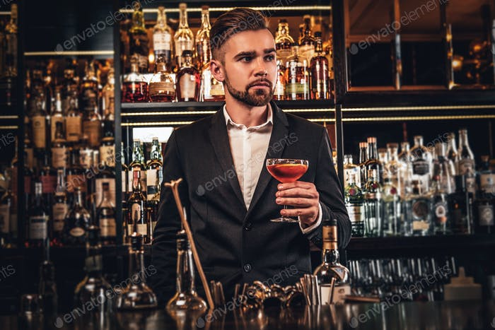 Elegant groomed man is drinking alcohol at the bar