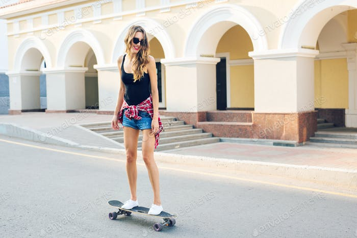 summer holidays, extreme sport and people concept - happy girl riding skateboard on city street