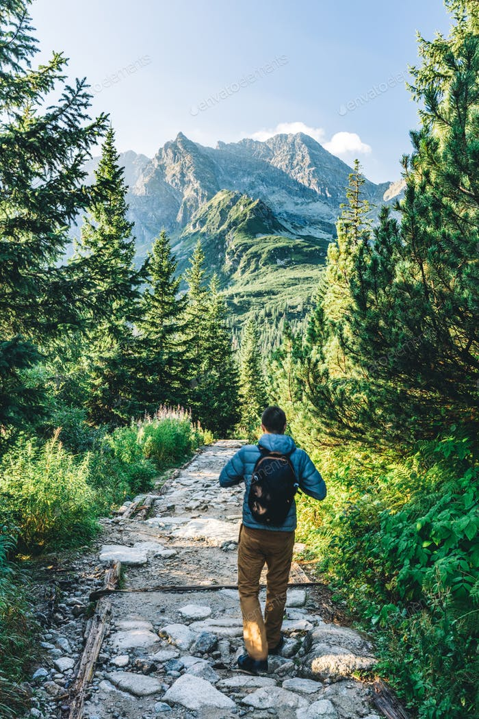 Man walking on hiking trail in Tatra mountains in Poland