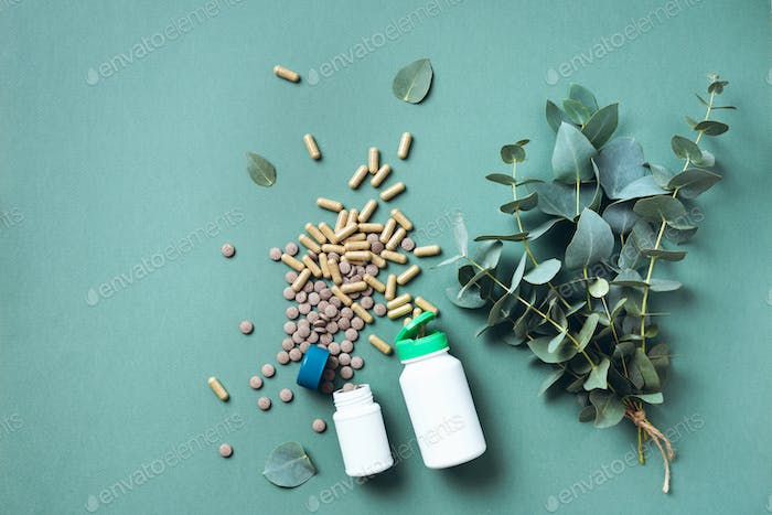 Eucalyptus capsules over green background with copy space. Prevention and health concept