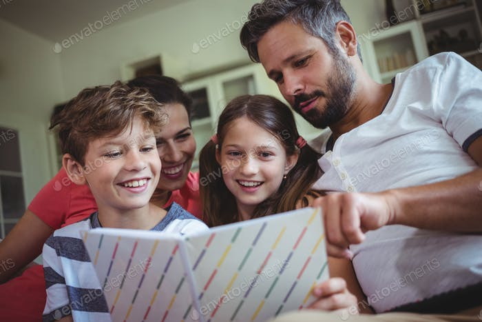 Smiling family looking at a photo album