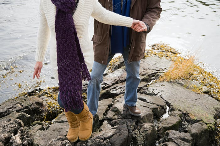 Mature couple climbing rocks