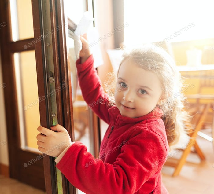 Three year old girl helps with housekeeping by cleaning the windows.