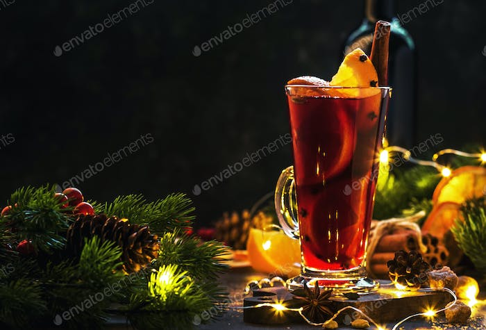 Christmas mulled red wine with spices and fruits in tall glass on wooden rustic table.
