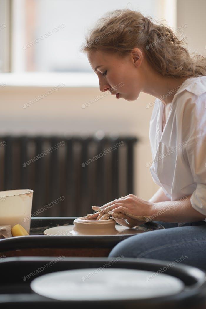 Mädchen macht Keramik aus Ton. Sie macht keramische Produkte aus weißem Ton mit verdrehten Töpfchen