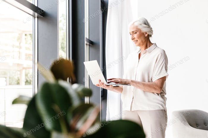 Satisfied mature business woman working on laptop