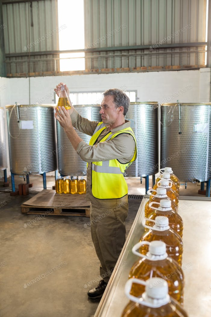 Male technician examining olive oil