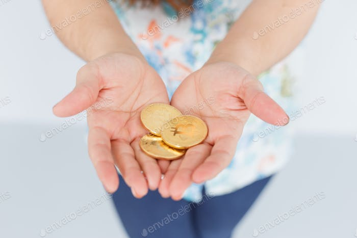 Bitcoin coins in woman hands